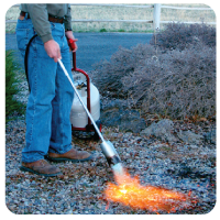 man using propane powered tool on the ground