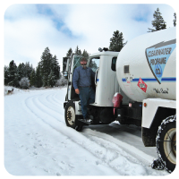 man in propane truck on a road covered with snow