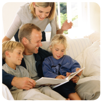 Parents with 2 young children reading book on the couch.